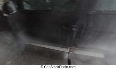 Point of view shot man washing car with high pressure washer...