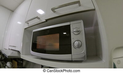 point of view shot of a man using a microwave oven in a...