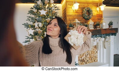 Point of view shot of good-looking brunette taking selfie on Christmas day holding camera and posing with hand gestures and gift box expressing positive emotions.