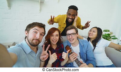 Point of view shot of multi ethnic group of cheerful friends taking selfie photos on smartphone camera while celebrating at party at home