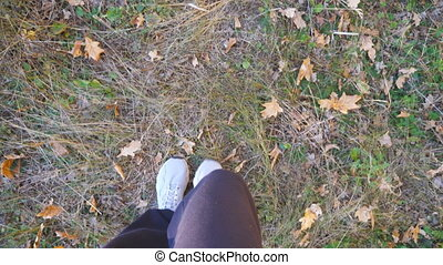 Point of view to male feet in sneakers steps along path outdoor. Legs of young guy goes on dry grass at early autumn. Guy walks at wild nature. Slow motion.