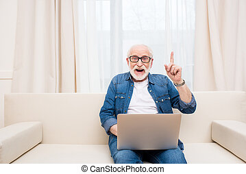 pointage, ordinateur portable, haut, doigt, utilisation, sourire, homme aîné