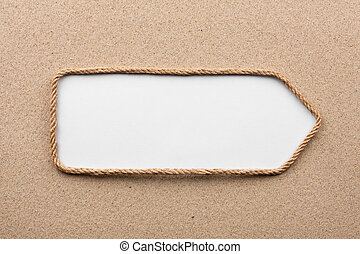 Pointer made of rope with a white background on the sand, with place for your text.