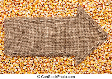 Pointer of burlap with place for your text, lying on a corn