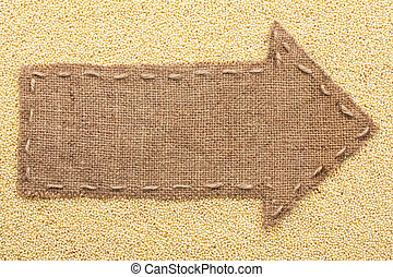 Pointer of burlap with place for your text, lying on a millet
