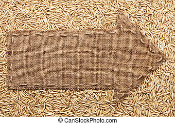 Pointer of burlap with place for your text, lying on a oat