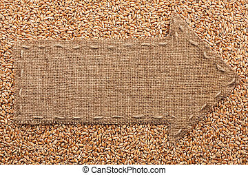 Pointer of burlap with place for your text, lying on a wheat