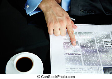 Pointing at article - Above angle of male hand pointing at...