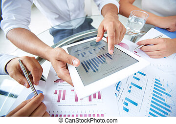 Close-up of businessman holding electronic document in touchpad and pointing at it