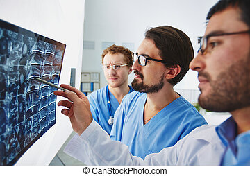 Pointing at x-ray - Young male doctor pointing at x-ray and...