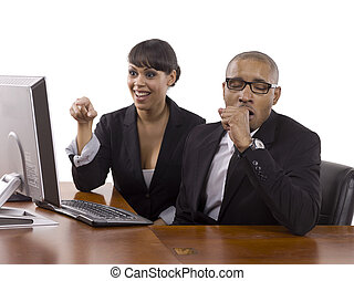 Smiling businesswoman pointing something on the computer screen showing it to her yawning coworker