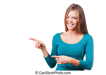 Pointing copy space. Beautiful young woman pointing away and making a face while standing against white background