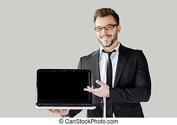 Pointing copy space on his laptop. Handsome young man in formalwear and glasses holding a laptop and pointing it while standing against grey background