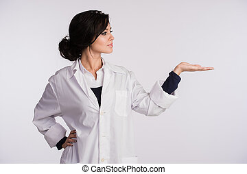 Pointing to blank copy space woman doctor nurse over white background