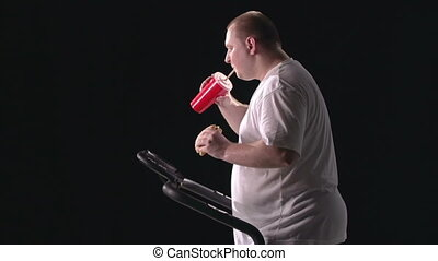 Pointless Workout - Side shooting of man eating fast food...