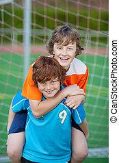 pojke, ge sig, på ryggen ritt, till, vän, på, fotboll gärde