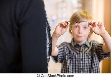 pojke, hållande glasögon, med, mor, in, förgrund, hos, butik