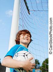 Pojke, litet, boll, medan, pol, holdingen, böjelse, nät, fotboll