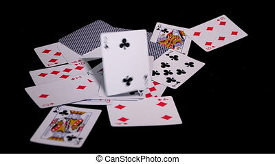 poker cards fly and fall on a black surface. - poker cards...