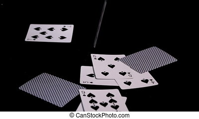 poker cards fly and fall on a black surface slow motion