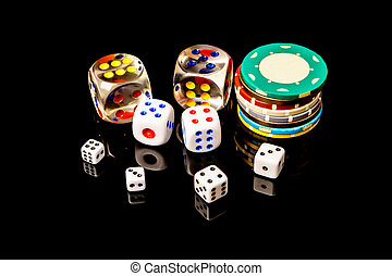 Poker chips and dice isolated on the black background .