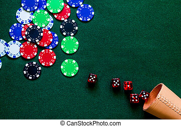 Poker chips and dice on a green gaming table top view copyspace