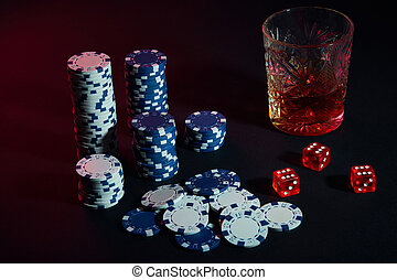 Poker chips and wine glass of cognac on dark table. Gambling
