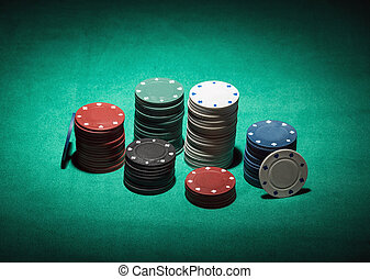 Colorful poker chips on green cloth, spot light