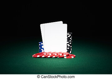 Poker chips on table with pair of blank cards