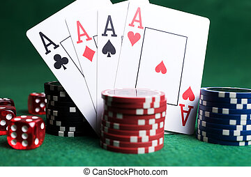 Poker chips, playing cards and red dice on green table