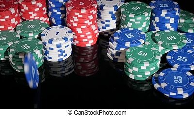 poker chips rolled into the casino on a black background. Slow motion