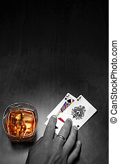 Poker player in mono with cards and whiskey in color