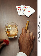 Poker player with cards cigar and whiskey