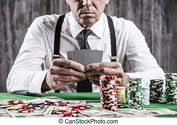 Poker player. Close-up of serious senior man in shirt and suspenders sitting at the poker table and holding cards  with money and  gambling chips laying all around him