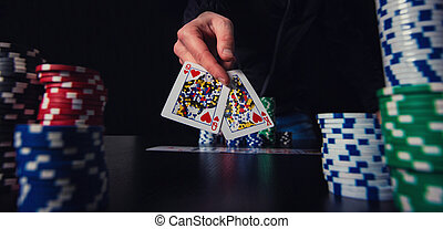poker player hand showing playing cards betting chips at the casino table