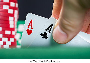 Poker player lifting the corners of two cards