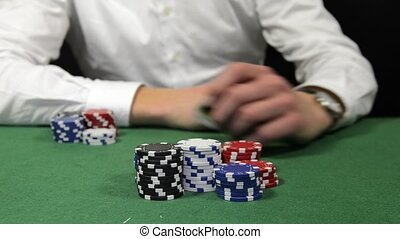 Poker player winning the pot with a pair of tens, sitting...