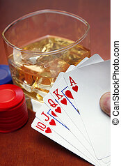 Poker player with cards and whiskey and chips