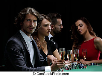 Poker players drink champagne on a black background