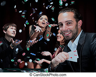 Poker players sitting around a table at a casino.