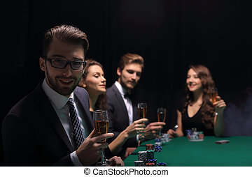 poker players with a glass of wine ,sitting at a table