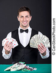 Portrait of a young smiling dealer with playing cards and money in hands.