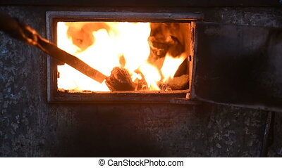 poking with a poker of coal in the furnace of the old...