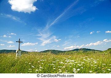 Poland, Bieszczady, Bystre. Old wayside cross on the meadow.