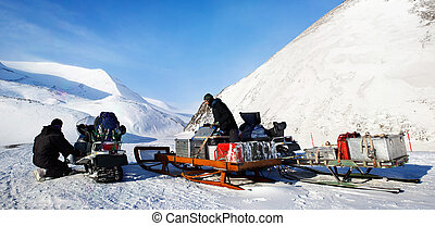 Polar Expedition - People preparing snowmobiles for an...