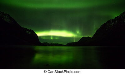 polar lights (aurora borealis) in a fjord in Norway in a...