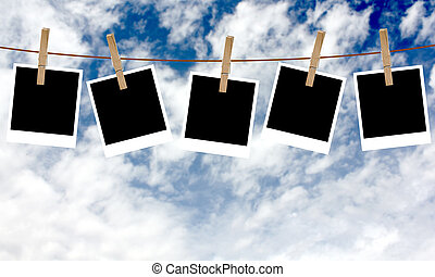Polaroid photos hanging on a rope with clothespins against ...