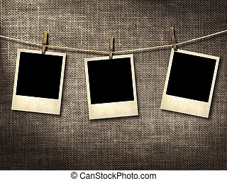 Polaroid style photographs hanging on a clothesline on a linen background