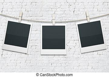 Polaroids on white brick - Three blank polaroids hanging on...