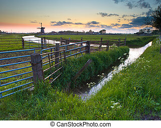 Typical dutch landscape with fences during sunset
